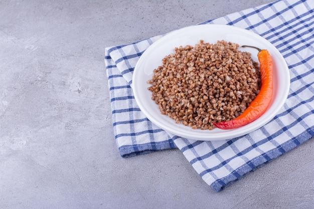 Delicioso trigo mourisco cozido com pimenta em uma toalha sobre fundo de mármore. foto de alta qualidade