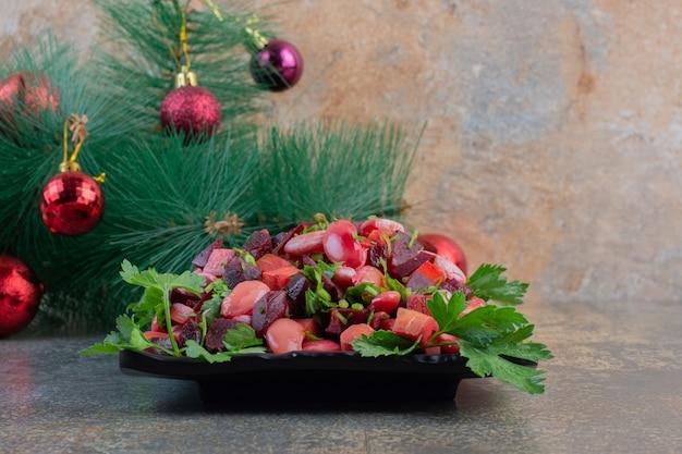 Delicioso vinagrete com bolas de natal em um fundo escuro. foto de alta qualidade