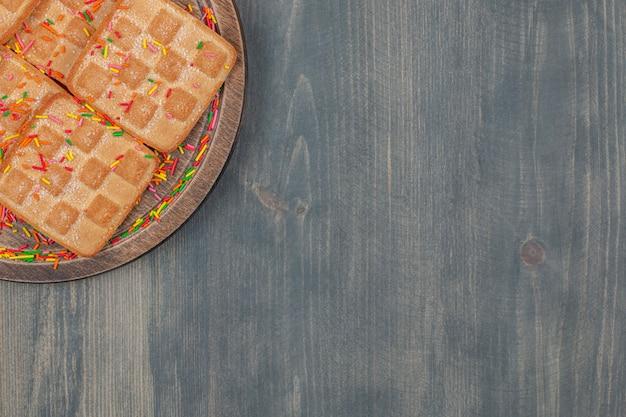 Delicioso wafer crocante com granulado em um prato de madeira
