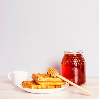 Delicioso waffle; pote de mel e café no café da manhã na mesa de madeira