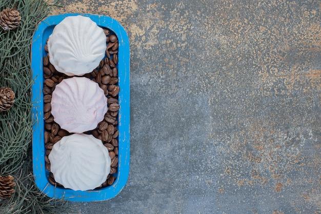 Delicioso zéfiro com grãos de café em um prato azul. foto de alta qualidade