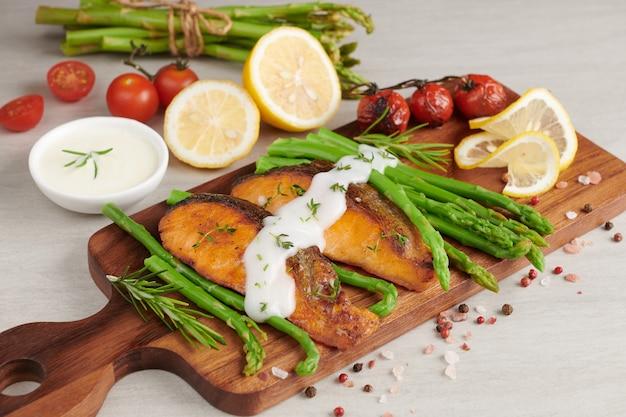 Deliciosos aspargos verdes sazonais e salmão fumado fatiado em prato rústico