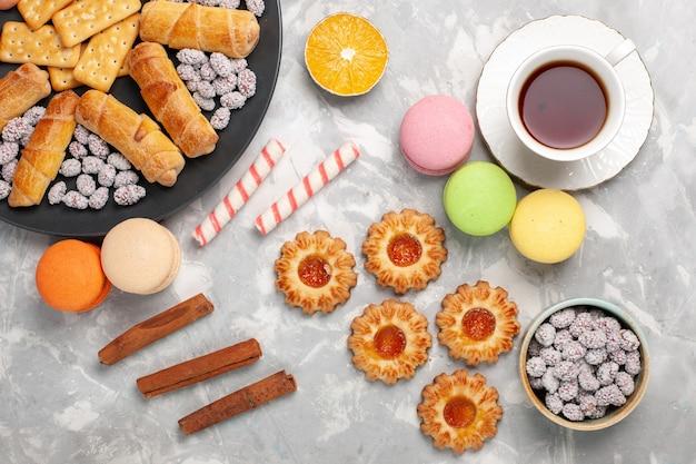 Deliciosos bagels com bolachas, macarons e uma xícara de chá na mesa de mesa de biscoito branco claro, deliciosos bagels com biscoitos doces crocantes