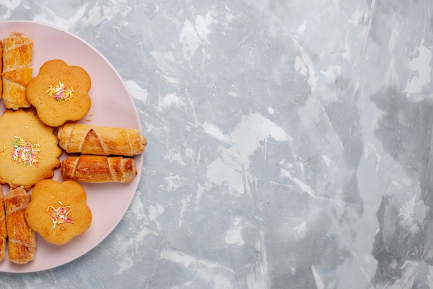 Deliciosos bagels com bolos dentro do prato na mesa branca de cima