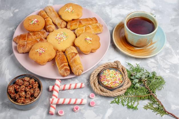 Deliciosos bagels com bolos e chá de frente na mesa branca
