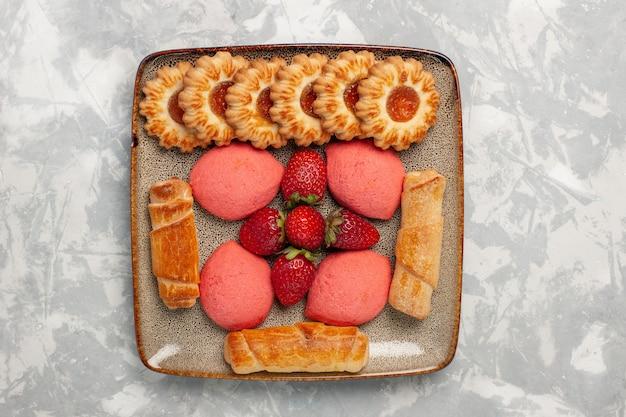 Deliciosos bagels de vista superior com bolos de morango e biscoitos na superfície branca