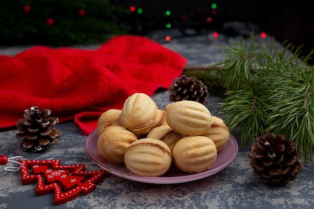 Deliciosos biscoitos amanteigados em forma de nozes com recheio de doce de leite condensado e nozes trituradas no fundo de uma árvore de natal e luzes. deleite de natal.