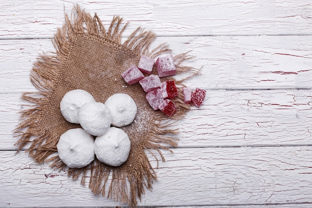 Deliciosos biscoitos brancos e vermelhos para chá servido na mesa de madeira branca