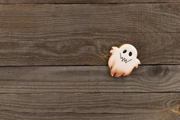 Deliciosos biscoitos caseiros de halloween com formas de fantasmas na velha mesa de madeira