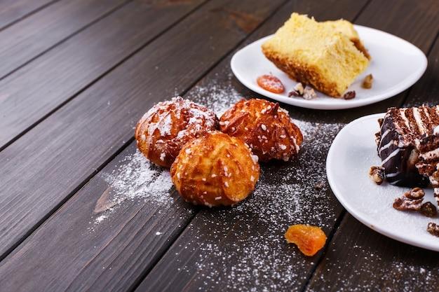 Deliciosos biscoitos, cheesecake e bolo de chocolate coberto com açúcar em pó