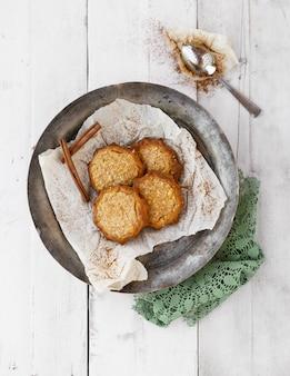 Deliciosos biscoitos com canela em uma tigela de metal e uma colher em uma superfície de madeira branca