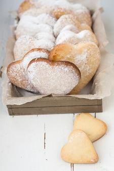 Deliciosos biscoitos com corações para dia dos namorados em uma superfície de madeira branca