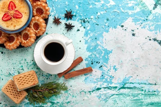 Deliciosos biscoitos com waffles e sobremesa de morango na superfície azul da vista de cima