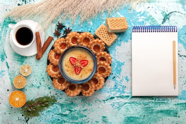 Deliciosos biscoitos de açúcar com waffles, xícara de café e sobremesa de morango na superfície azul de cima