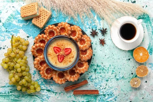 Deliciosos biscoitos de açúcar com waffles, xícara de uva de café e sobremesa de morango na mesa azul com vista de cima