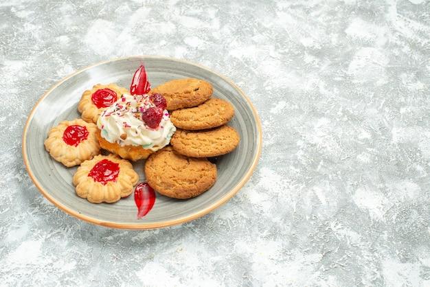 Deliciosos biscoitos de areia com biscoitos e bolo de creme no espaço em branco de frente