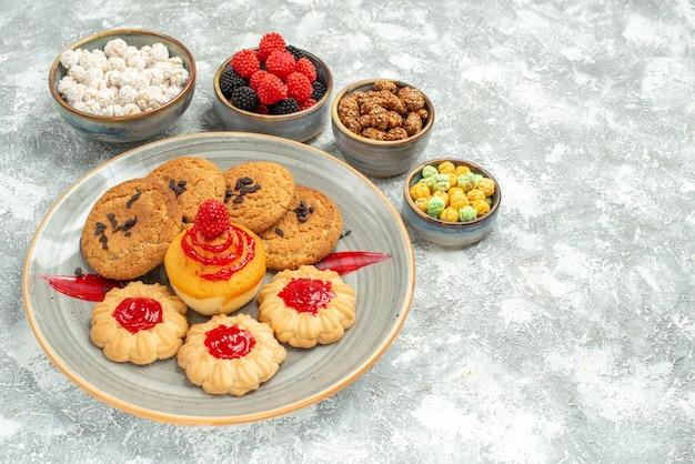Deliciosos biscoitos de areia com biscoitos e doces no espaço em branco de frente