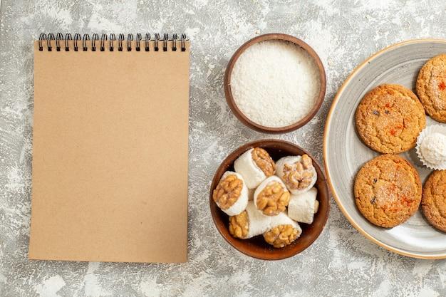 Deliciosos biscoitos de areia com doces na mesa branca de cima