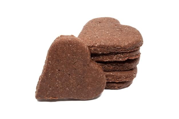 Deliciosos biscoitos de chocolate caseiros em forma de coração, empilhados, isolados em uma parede branca.