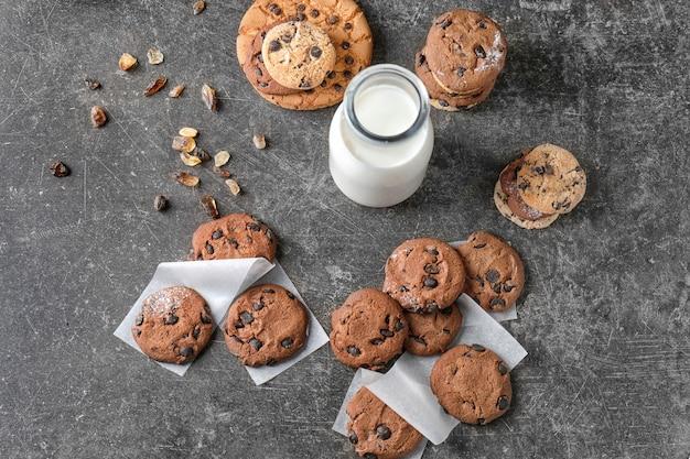 Deliciosos biscoitos de chocolate e leite em garrafa na superfície escura