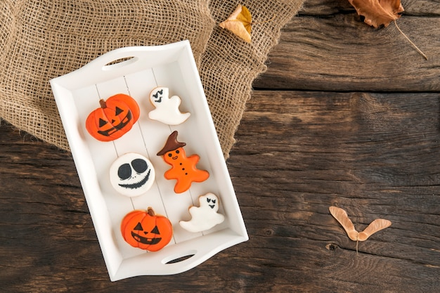 Deliciosos biscoitos de gengibre branco e laranja em uma placa de madeira branca sobre uma superfície marrom. pão de mel de halloween, copie o espaço
