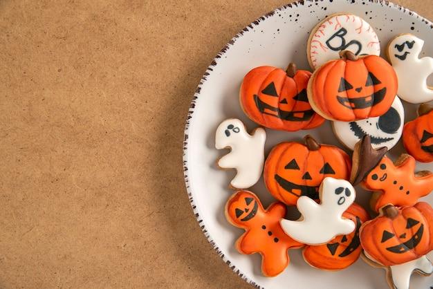 Deliciosos biscoitos de gengibre de diferentes formas para o halloween em uma superfície marrom. fechar-se. copie o espaço.