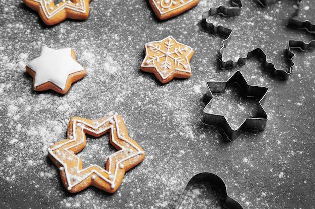 Deliciosos biscoitos de natal com açúcar de confeiteiro espalhado na superfície cinza