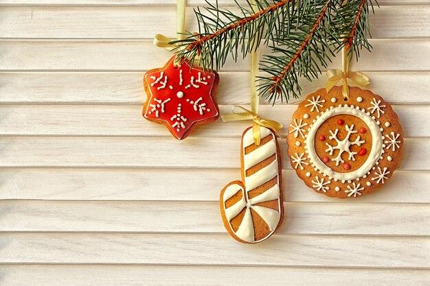 Deliciosos biscoitos de natal pendurados em um galho de árvore do abeto contra um fundo de madeira
