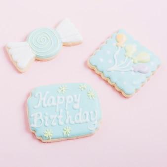 Deliciosos biscoitos decorados com formas diferentes no fundo rosa