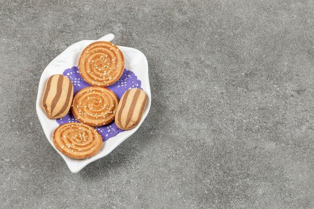 Deliciosos biscoitos listrados de chocolate e biscoitos de gergelim em prato branco