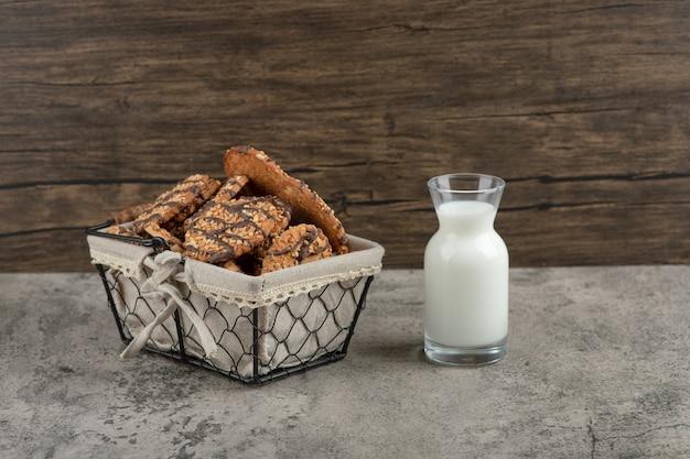 Deliciosos biscoitos multigrãos frescos com cobertura de chocolate em uma cesta com uma jarra de vidro de leite.