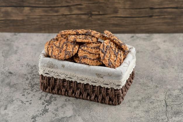Deliciosos biscoitos multigrãos frescos com cobertura de chocolate na cesta.
