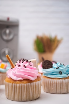 Deliciosos bolinhos caseiros com creme colorido e cobertura com doces e biscoitos de chocolate.
