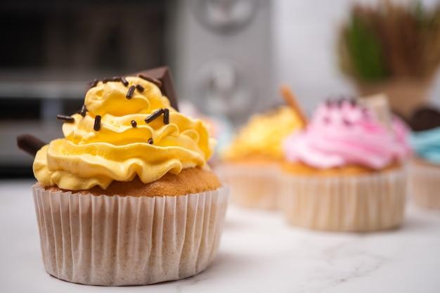 Deliciosos bolinhos caseiros com creme colorido e cobertura com doces