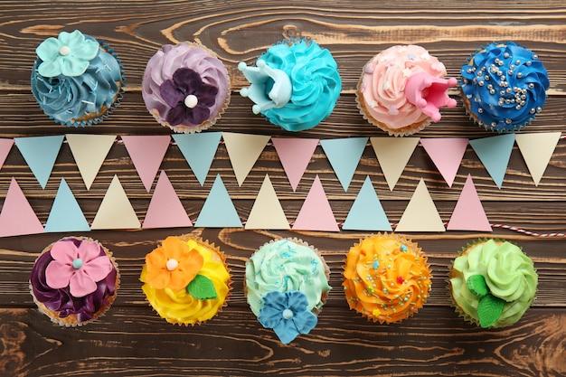 Deliciosos bolinhos coloridos com decoração de festa em madeira