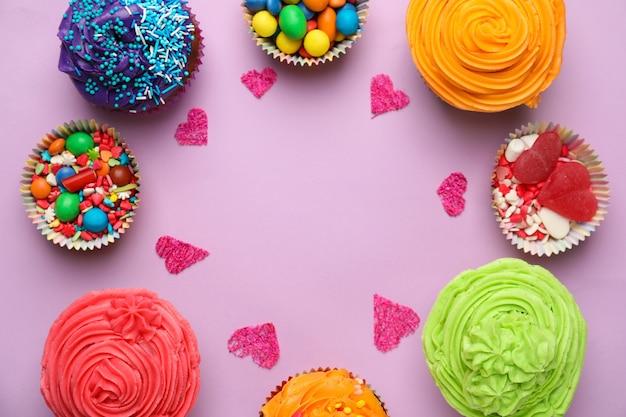 Deliciosos bolinhos coloridos com doces na superfície colorida