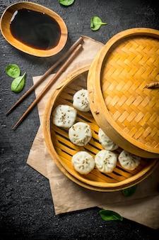 Deliciosos bolinhos de manta com carne em um vaporizador de bambu na mesa rústica preta.