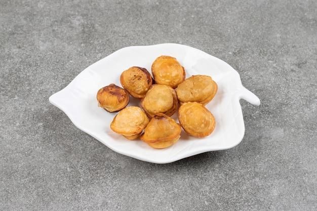 Deliciosos bolinhos fritos em prato branco