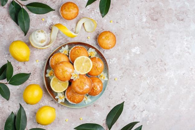 Deliciosos bolos caseiros de limão caseiro com limões em um prato na luz