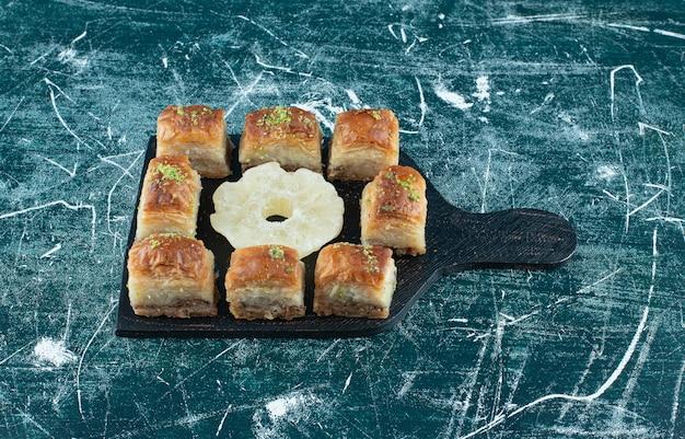 Deliciosos bolos com abacaxi seco em uma placa escura. foto de alta qualidade