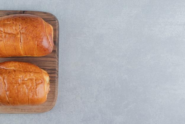 Deliciosos bolos com salsichas na placa de madeira.