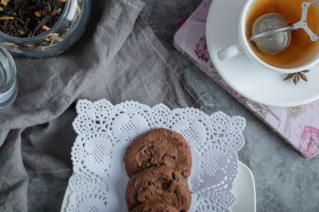Deliciosos bolos com uma xícara de chá na toalha de mesa cinza.