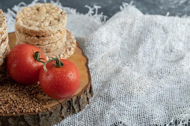 Deliciosos bolos de arroz, tomates e trigo sarraceno cru na peça de madeira