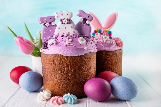 Deliciosos bolos de páscoa decorados com cobertura de coelho, caramelo e merengue, e ovos de galinha em turquesa com espaço de cópia