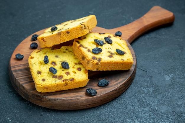 Deliciosos bolos de passas fatiados com passas frescas em um espaço azul escuro com vista frontal