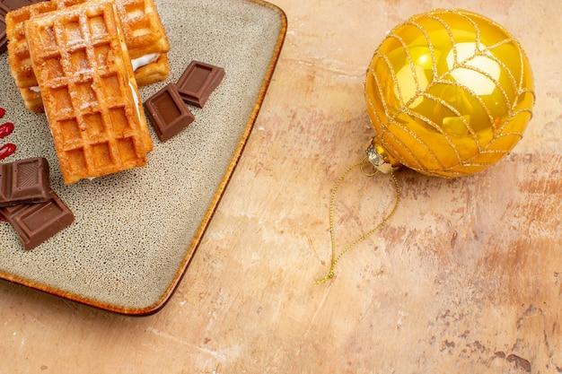 Deliciosos bolos de waffle de frente com brinquedos de árvore de ano novo em um fundo claro torta doce creme sobremesa bolo