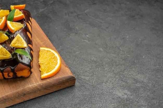 Deliciosos bolos decorados com laranja e chocolate em uma tábua de cortar na mesa preta