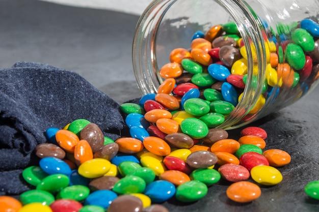 Deliciosos bombons de chocolate coloridos em frasco de vidro derramado