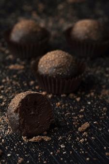 Deliciosos bombons de chocolate com as migalhas na superfície preta