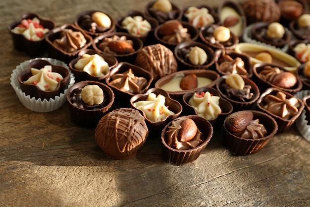 Deliciosos bombons de chocolate na mesa de madeira, close-up